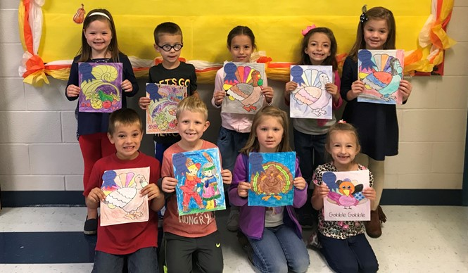 "Kindergarten students proudly show off their ribbons as winners of the November ""Artist of the Month"" at ECC."