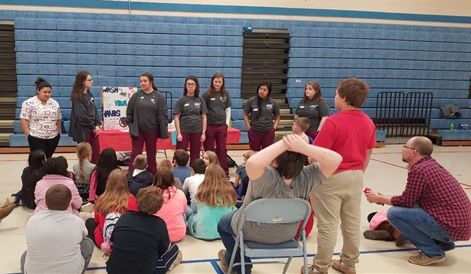CCATC health sciences students talk about hand washing at the AES Health Fair.