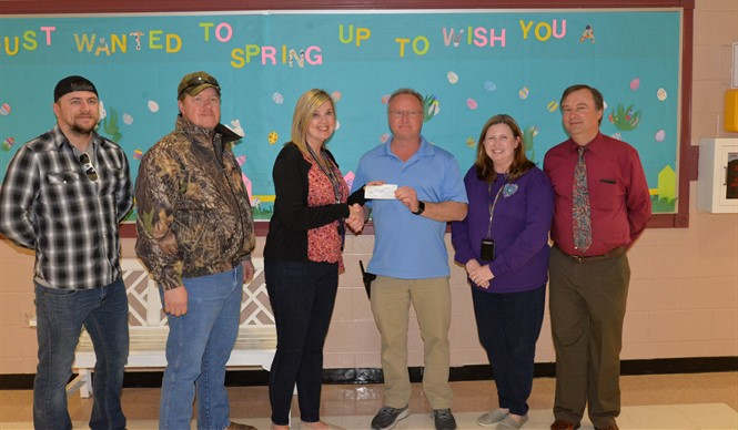 Albany Lions Club President Tammie Conner presents AES Principal Tim Armstrong a check to purchase six HP Chromebooks for the students at AES.