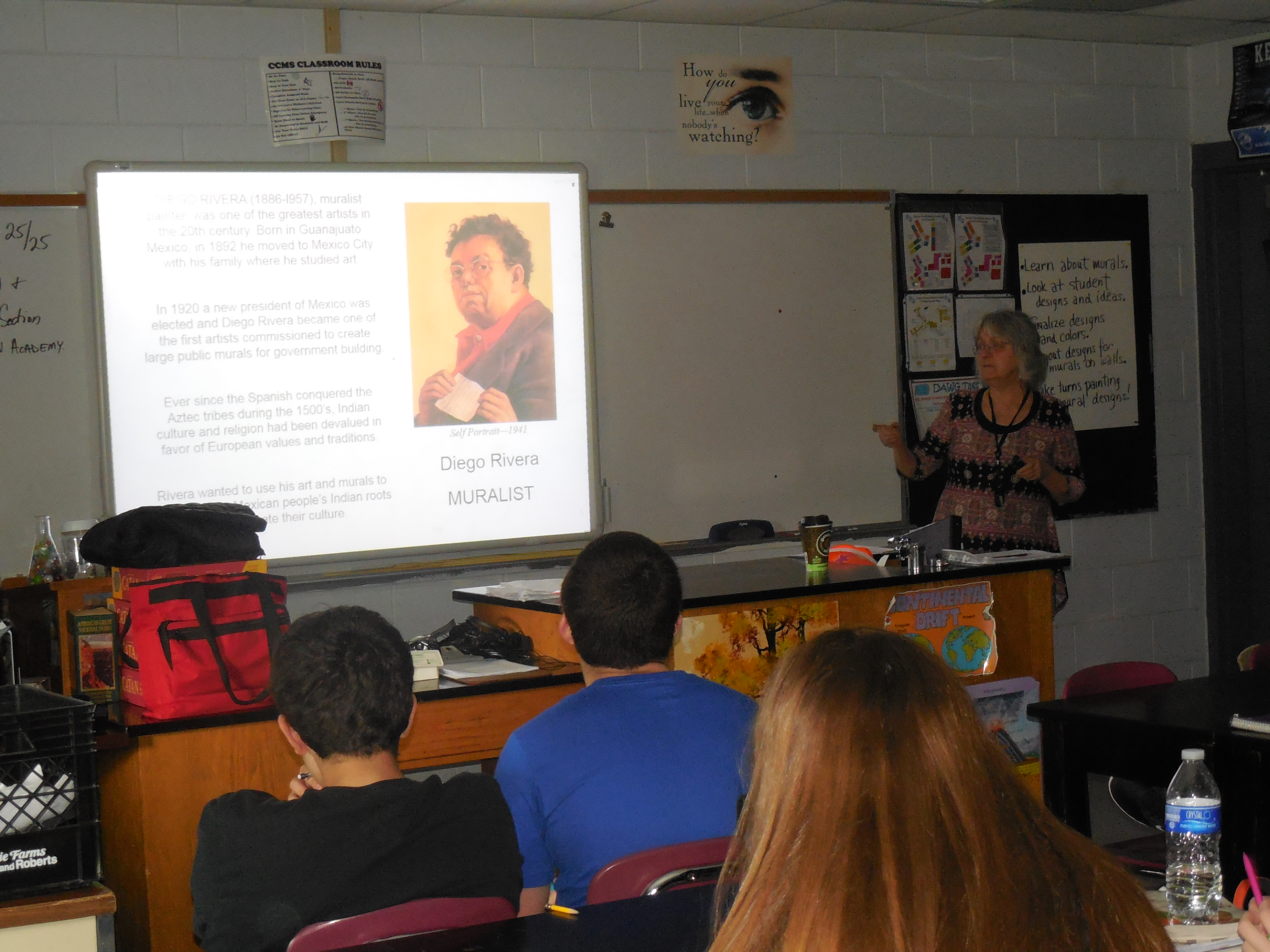 Ms. Pat Ritter is pictured below discussing murals with the students and looking over their sketches on the first day.